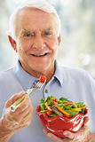 Senior Man Smiling At Camera And Eating Salad