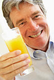 Senior Man Smiling At Camera And Drinking Orange Juice