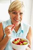 Middle Aged Woman Eating A Bowl Of Fruit