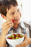 Young Boy Eating Bowl Of Fresh Fruit