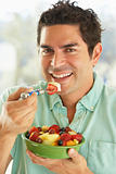 Mid Adult Man Holding A Bowl Of Fresh Fruit Salad Smiling At The