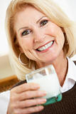 Senior Woman Holding A Glass Of Milk, Smiling At The Camera