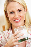 Mid Adult Woman Holding Glass Of Milk, Smiling At Camera