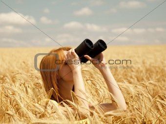 Redhead girl with binocular at wheat field.