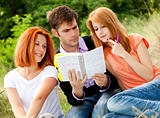 Three students at outdoor doing homework.