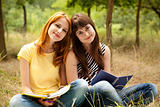 Two girlfriends doing homework at the park.