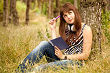 Young teen girl doing homework at the park.