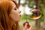 Redhead girl inflate soap bubble.