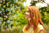 Redhead girl in the park under soap bubble rain.