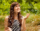 Brunette girl in the park under soap bubble rain.