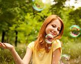 Redhead girl in the park under soap bubble rain.