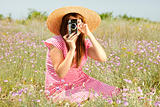 Retro style girl at countryside with camera.