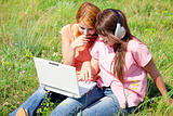 Two girlfriends at countryside with laptop and computer.