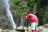 photographer taking picture of waterfall