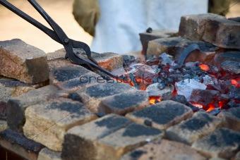 tongs with hot iron horseshoe