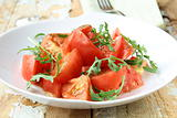 Ripe tomato salad with arugula in a rustic style on a wooden table