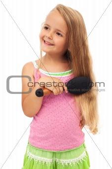 Little girl combing hair