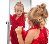 Little girl trying dress in front of mirror