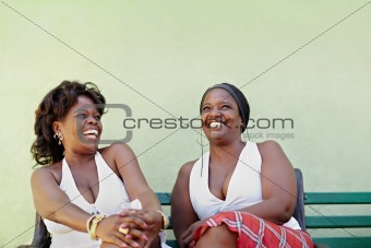black women with white dress laughing on bench