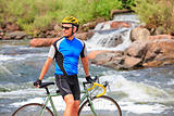 Cyclist standing by the river