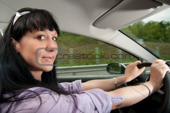 Beautiful young woman drives a car on a highway