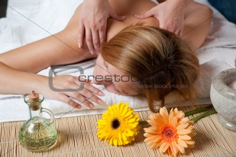 Beautiful young woman having a massage in wellness centre - girl