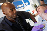 Paramedic listening to patients heartbeat