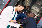 Hospital doctor taking notes as paramedics arrive with patient