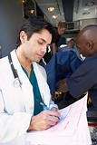 Doctor taking notes as paramedics unload patient