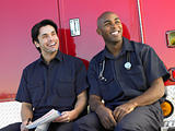 Two paramedics cheerfully doing paperwork, sitting by their ambu