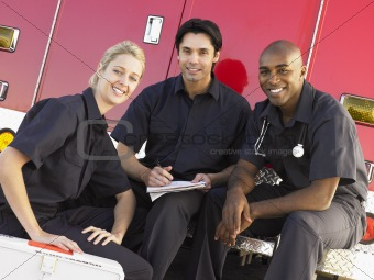 Three paramedics chatting and doing paperwork, sitting by their