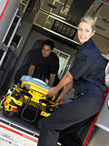 Two paramedics cheerfully removing empty gurney from ambulance