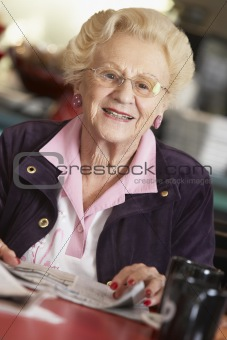 Senior woman reading newspaper