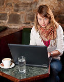 Morning coffee in internet cafe - Beautiful young girl checking news on web and drinking coffee