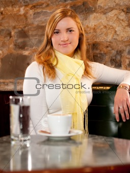 First cappuccino - Beautiful young caucasian girl drinking coffee in a bar in early morning