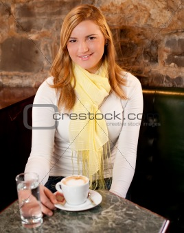 First capuccino - Beautiful young caucasian girl drinking coffee in a bar in early morning