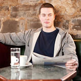 Morning coffee and news - Handsome young man reading newspaper