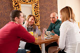 Man just arrived in a caffee where three friends were expecting him