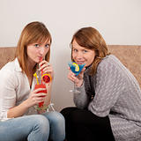Two pretty friends celebrating with colorful cocktails on white background