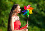woman with long hair holding a multicolored pinwheel in a park