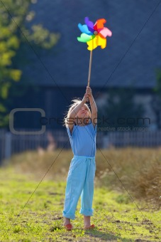 boy with long blond hair playing with pinwheel outside