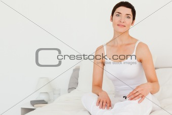 Close up of a woman sitting on her bed