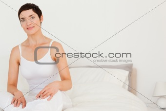 Close up of a young woman sitting on her bed
