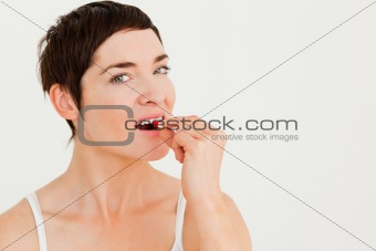 Close up of a young woman taking a pill