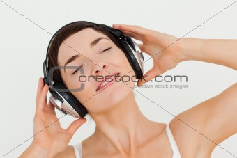 Close up of a delighted brunette listening to music