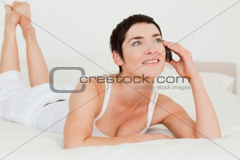 Cute woman calling while lying on her bed