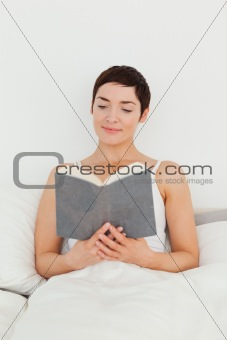 Smiling brunette reading a book