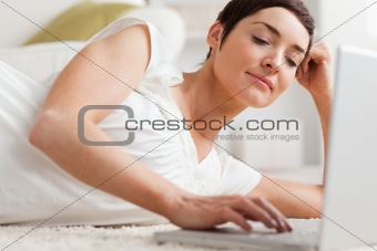 Close up of a quiet woman relaxing with a laptop