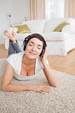 Portrait of a delighted brunette listening to music