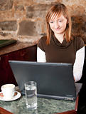 Morning coffee in internet cafe - Beautiful young girl checking news on web and drinking coffe